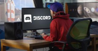 A child looks at a screen on to which has the Discord logo composited on to it