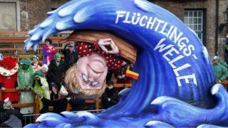 A carnival float with a papier-mache caricature shows German chancellor Angela Merkel on a boat being overturned by a wave labelled 'refugee wave'.