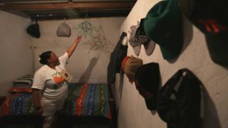 Mujer sostiene un adorno dentro de un cuarto.