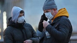 Two men wear face masks in London's Trafalgar Square