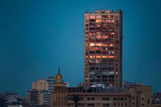 A tall tower block stands next to a domed mosque in a built-up part of the city of Cairo. The sky is a dark blue and the tower's windows are illuminated by the sun in a bright orange. Egypt - Wednesday 20 February 2019