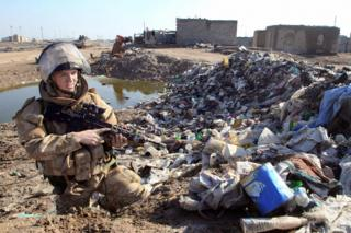 2007: A British troop in Basra patrols a rubbish-strewn area