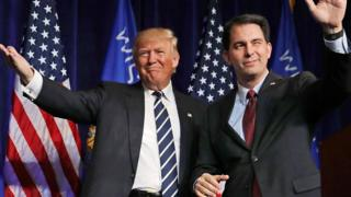 Republican presidential nominee Donald Trump (L) is welcomed to the stage by Wisconsin Governor Scott Walker during a campaign rally at the W.L. Zorn Arena November 1, 2016 in Altoona, Wisconsin.