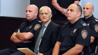 Dragan Vasiljkov sits flanked by policemen