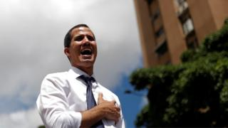 Venezuelan opposition leader Juan Guaido, who many nations have recognised as the country's rightful interim ruler, sings the national anthem during a rally