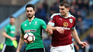 Lincoln's Samuel Habergham and Sam Vokes from Burnley fight for the ball