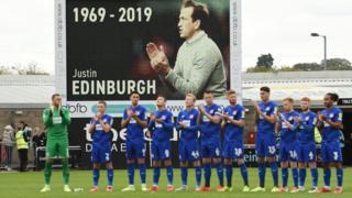 Football players hold an applause for Justin Edinburgh.