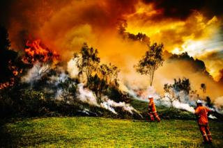 Firefighters battle a blaze on a hill