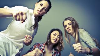 Tres mujeres en actitud de pelea contra un enemigo común.
