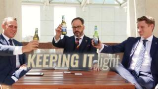 A screenshot of the Bible Society video featuring two MPs and a host holding Coopers beers