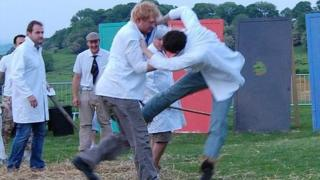 Two men compete at shin-kicking