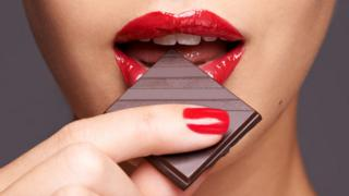 A woman's lips biting a piece of chocolate