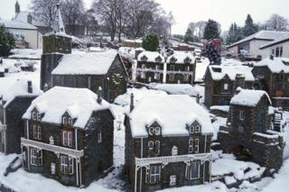 Rawson Robinson clears snow from a model village