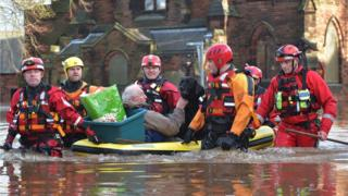 A pensioner and his dog are taken to safety on a dinghy by emergency services