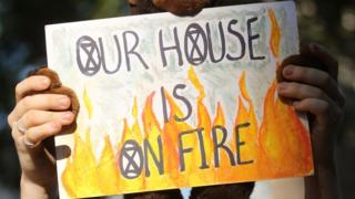 A protester holds placard saying 'our house is on fire'