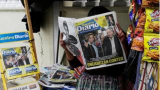 A woman reads a newspaper showing Sandra Torres and Alejandro Giammattei on 17 June, 2019