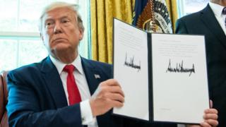 US President Donald Trump holds a copy of an executive order for additional sanctions against Iran at the White House on 24 June 2019