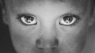 Los ojos de un niño con la cara sucia