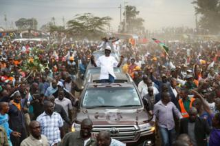 Raila Odinga sits on the roof of his car, surrounded by supporters.
