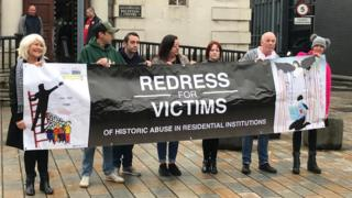 Victims campaigners hold a banner that reads: Redress for victims of historic abuse in residential institutions