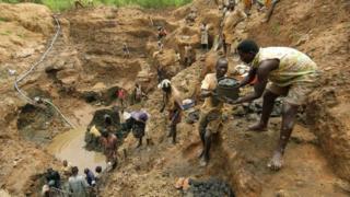 Les travailleurs forment une chaîne humaine pour relayer des seaux de boue et de pierres dans une mine d'or à Iga Barriere le 18 juin 2003, à l'est de la RD Congo (archives)