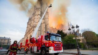 Bombeiro e caminhão aparecem em ação com a catedral pegando fogo ao fundo