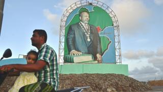 A motorcyclist rides past a poster of Ismail Omar Guelleh, President of Djibouti in Djibouti