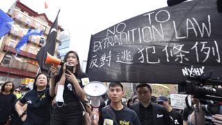 """在紐約,她身穿一身黑衣,T恤上寫著:""""我係香港人(我是香港人)""""。"""