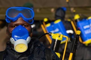 A soldier prepares equipment to spray crops