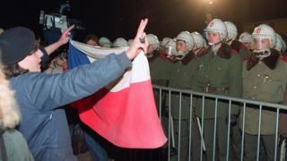 A female student holds a Czechoslovakian flag as she and hundreds others face riot police 19 November 1989 in downtown Prague