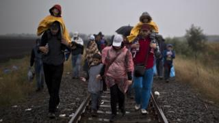 Syrian refugees walk on a railway track