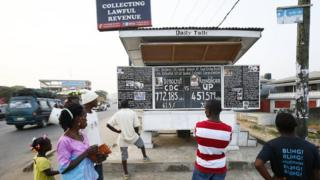 "People looking at the ""Daily Talk"" chalkboard paper in Monrovia, Liberia - Sunday 31 December 2017"