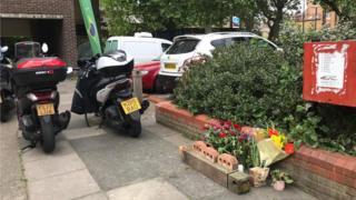 Foto mostra homenagem com flores para brasileiro morto em Londres no local do crime