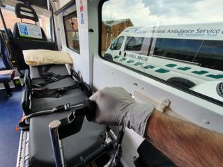 A carer holds a stretcher in an ambulance