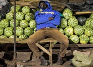 in_pictures A trader sleeps by his melon stall in Kampala, Uganda - Wednesday 8 April 2020
