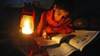طفلة عراقية تذاكر على ضوء مصباح كيروسين