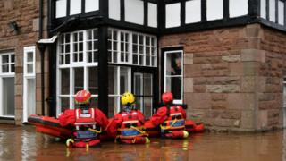Rescuers up to their waist in floodwater outside a house