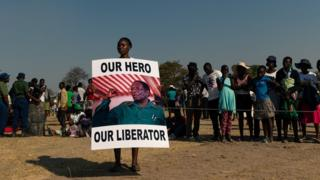 A young woman holds a placard reading 'Our hero, our liberator' villager queue to view the coffin of late former Zimbabwean president Robert Mugabe lying in state at Murombedzi Growth Point, about 107 km northwest of Harare, Zimbabwe, on September 16, 2019, as people have been accorded the opportunity to view Mugabe's body a week after his death. - The remains of former Zimbabwe president Robert Mugabe were taken to his village for a wake on September 16, a family member said, as his final burial is prepared in about a month. Mugabe died a week ago aged 95 in Singapore, nearly two years after he was ousted in a 2017 coup that ended nearly four decades of increasingly autocratic rule. After a state funeral on September 14 in the capital Harare attended by African leaders, his body went to his rural village of Kutama, 90 kilometres (55 miles) to the west, to allow villagers to pay tribute and bid farewell.