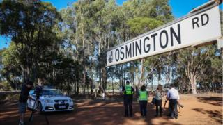 Media film a property from a police roadblock where police are investigating the deaths of seven people in suspected murder-suicide in Osmington, east of Margaret River, 260km south west of Perth, Australia, 11 May 2018.