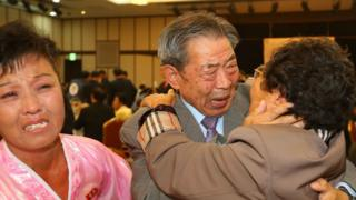 """South Korean Min Ho-Sik (C), 84, hugs his North Korean relative Min Eun-Sik (R), 81, during a separated family reunion meeting at the Mount Kumgang resort on the North""""s southeastern coast on October 20, 2015."""