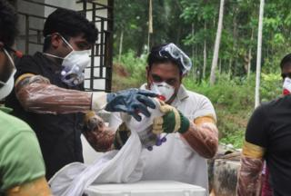 Animal Husbandry department and Forest officials deposit a bat into a container after catching it inside a well at Changaroth in Kozhikode in the Indian state of Kerala on May 21, 2018.