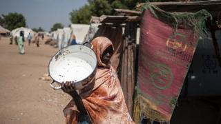 Un femme dans un camp de déplacés à la recherche d'eau.