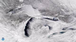 "Satellite image from above the Great Lakes showing parallel rows of cumulus clouds also known as ""cloud streets"""