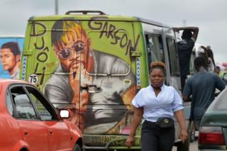 People and cars are seen on the road next to a minibus painted with a portrait of DJ Arafat.