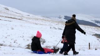 Семья с санками на фоне гор.