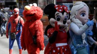 Costumed characters in Times Square: Spiderman, Elmo, Minnie Mouse, Elsa from Frozen