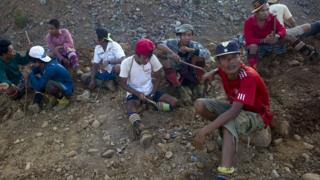 A group of men are sat in a pile of rubble, with hand held diggers