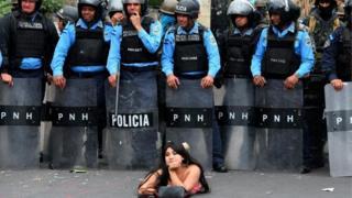 Seorang pengunjuk rasa berbaring di jalan di depan petugas polisi selama demonstrasi menentang pemilihan ulang Presiden Hernandez yang diperebutkan di Honduras