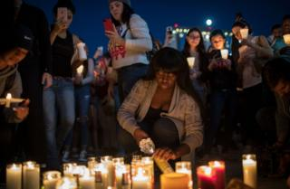 A woman lights a candle in Las Vegas as a tribute to those killed in a gun attack in the city