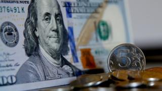 рублевая монета и доллар